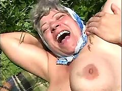 Greyhaired granny has sex on grass
