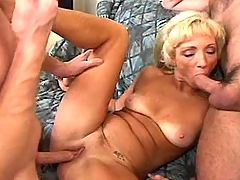 Two men share blonde mature in orgy